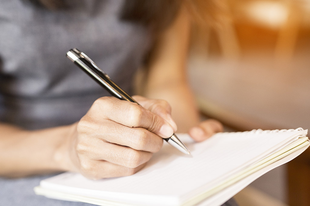 woman writing in a notebook with a pen