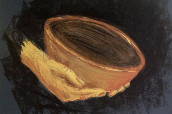 a pair of hands holding a clay bowl on a dark background